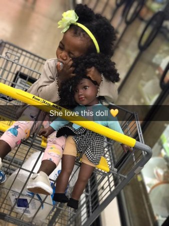 A little girl with a doll that looks just like her.